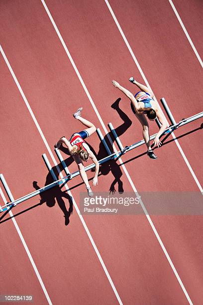 runners jumping hurdles on track - rivaliteit stockfoto's en -beelden