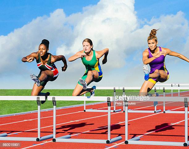 Runners jumping over hurdle on track