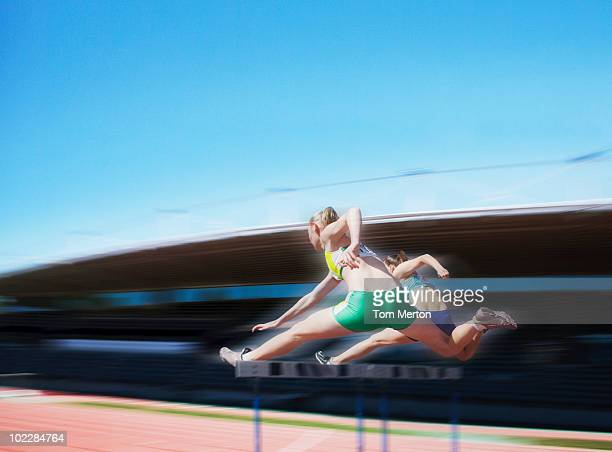 Runners jumping over hurdles
