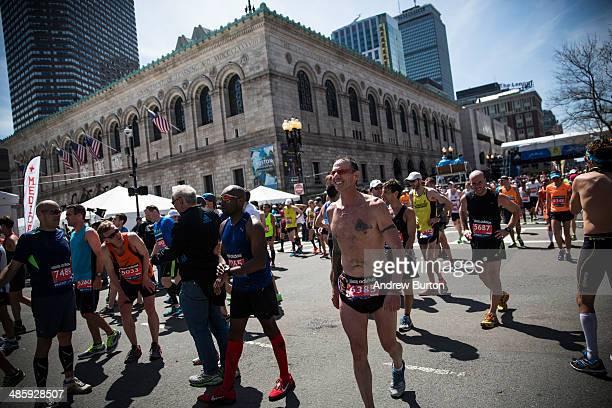 Runners limp down the street after finishing the Boston Marathon on April 21 2014 in Boston Massachusetts Today marks the 118th Boston Marathon...