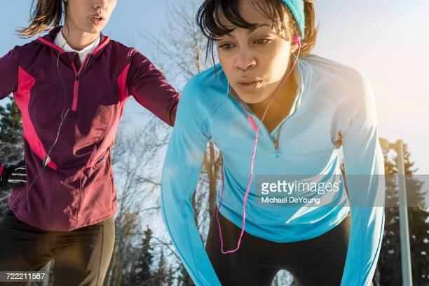 Runners listening to earbuds and resting