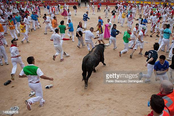 Runners make space for a Cebada Gago fighting bull as it enters the bullring on the third day of the San Fermin runningofthebulls on July 9 2012 in...