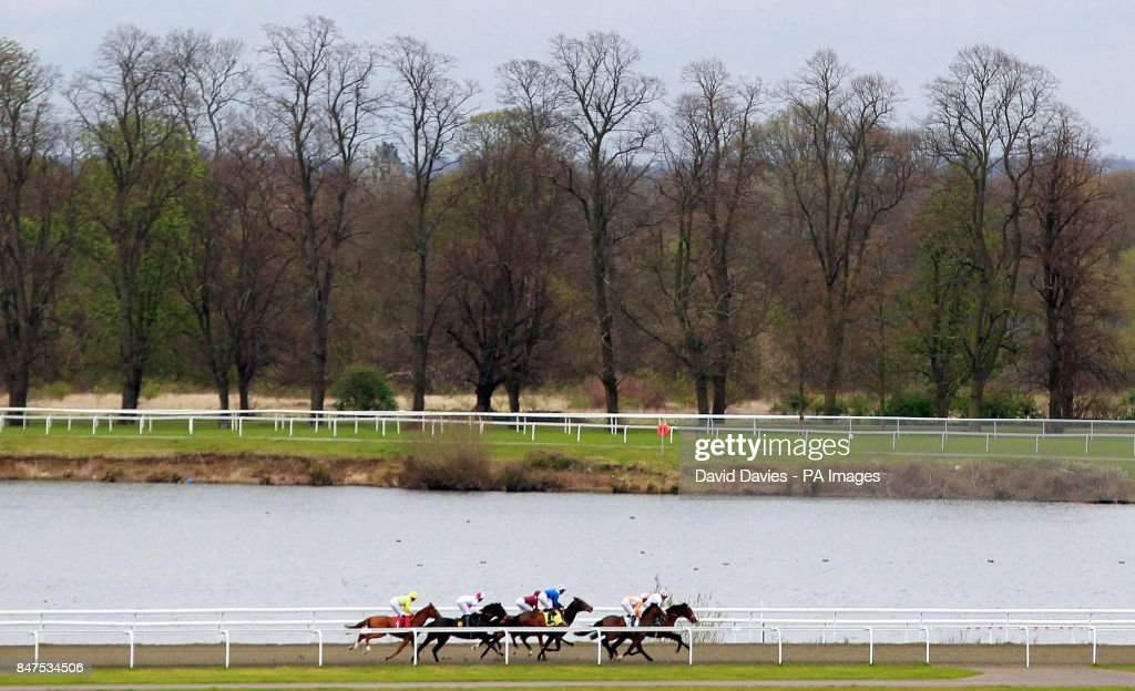 Horse racing easter family fun day kempton park racecourse runners make their way along the back straight in the betfred double delight conditions stakes at negle Gallery