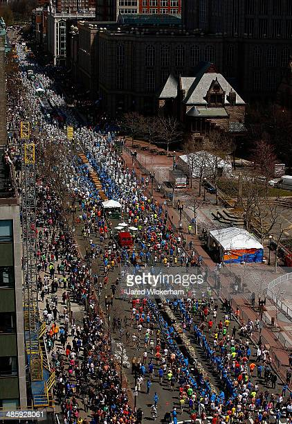 Runners make their way down Boylston Street to receive their medals after competing in the 2014 BAA Boston Marathon on April 21 2014 in Boston...