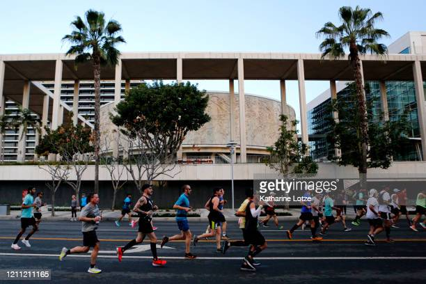 Runners make their way down Grand Avenue in front of the Mark Taper Forum during the 2020 Los Angeles Marathon on March 08 2020 in Los Angeles...