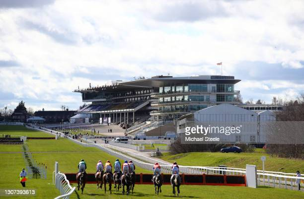 Runners make their way down the home straight towards the empty grandstands on the first circuit during the Sky Bet Supreme Novices' Hurdle on Day...