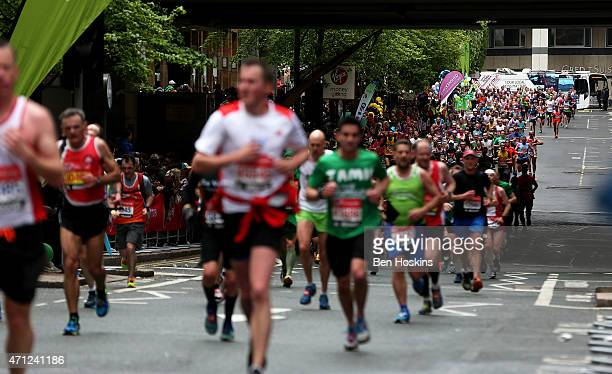 Runners make their way through Canary Wharf during the Virgin Money London Marathon on April 26 2015 in London England