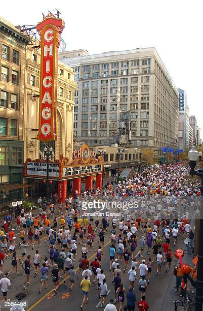 Runners move past the Chicago Theatre on State street during the LaSalle Bank Chicago Marathon October 12 2003 in Chicago Illinois