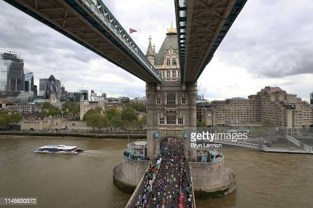 Runners of the London Marathon are seen crossing Tower Bridge during the Virgin Money London Marathon at United Kingdom on April 28 2019 in London...