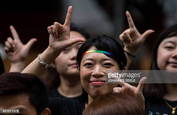 Runners of the Shanghai Pride Run make signs with their fingers while wearing rainbow shoelaces at the start of the race in Shanghai on June 18 2016...