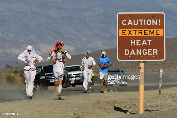 Runners pass a heat danger warning sign during the AdventurCORPS Badwater 135 ultramarathon race on July 15 2013 in Death Valley National Park...