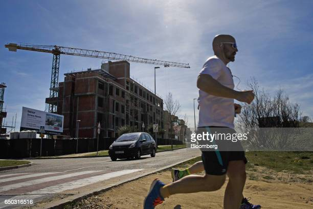 Runners pass a residential construction site operated by Neinor Homes SLU in the San Sebastian de los Reyes district of Madrid Spain on Wednesday...