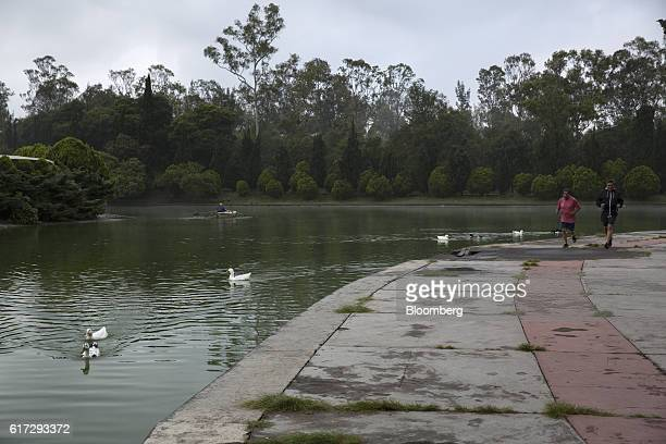 Runners pass a visitor in a row boat while running along a path next to an artificial lake inside the second section of Chapultepec Park in Mexico...