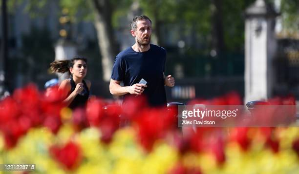 Runners pass Buckingham Palace on April 26 2020 in London England The 40th London Marathon was due to take place today with thousands of runners due...