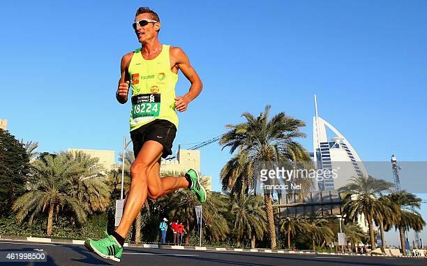 Runners pass Burj Al Arab during the Standard Chartered Dubai Marathon on January 23 2015 in Dubai United Arab Emirates