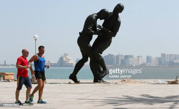 Runners pass by a bronze sculpture by French Algerian born artist Adel Abdessemed during its installation on October 4 2013 on the Corniche in Doha...