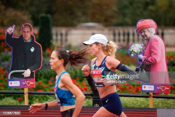 Runners pass cutouts of Britain's Prince William Duke of Cambridge and Britain's Queen Elizabeth II during the women's race of the 2020 London...