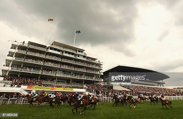 Runners pass the grandstand at the finish of The totesportcom 'Dash' Race run at Epsom Racecourse on June 7 in Epsom England