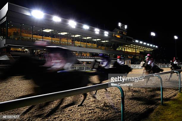 Runners pass the grandstand in The Coral Mobile 'Just Three Clicks To Bet' Handicap Stakes at Wolverhampton racecourse on January 09 2014 in...