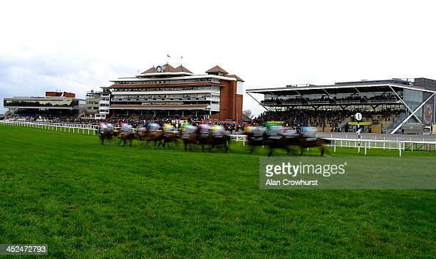Runners Pass the grandstands in The Pertemps Network Handicap Hurdle Race at Newbury racecourse on November 29 2013 in Newbury England