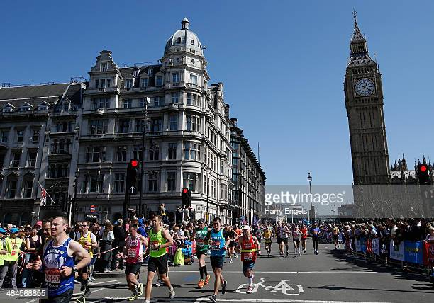 Runners pass the Houses of Parliament during the Virgin Money London Marathon on April 13 2014 in London England
