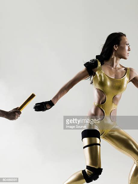 runners passing a relay baton - passing sport stock pictures, royalty-free photos & images