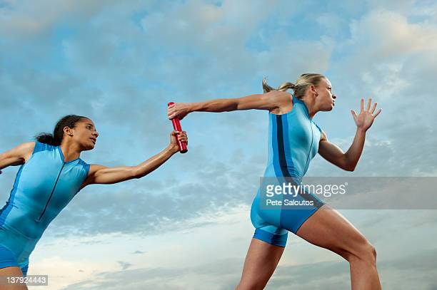 runners passing baton in relay race - relay baton stock photos and pictures