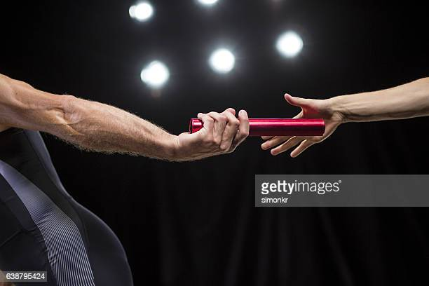 runners passing baton - passing sport stock pictures, royalty-free photos & images