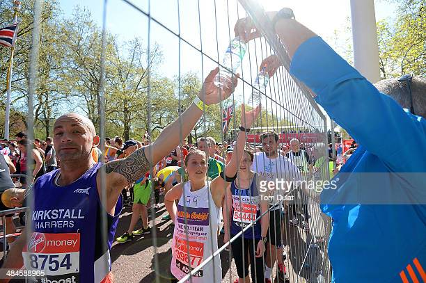 Runners pick up bottles of water during the Virgin Money London Marathon on April 13 2014 in London England