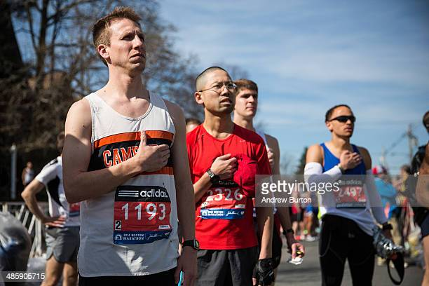Runners place their hands over their hearts during a singing of the National Anthem at the beginning of the Boston Marathon on April 21 2014 in...
