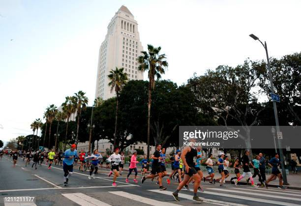 Runners prepare to turn onto 1st Street from Spring Street near City Hall during the 2020 Los Angeles Marathon on March 08 2020 in Los Angeles...