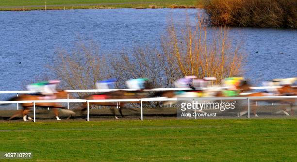 Runners race down the back straight in The Book Now For Silver Cup Day National Hunt Flat Race at Kempton Park racecourse on February 16 2014 in...