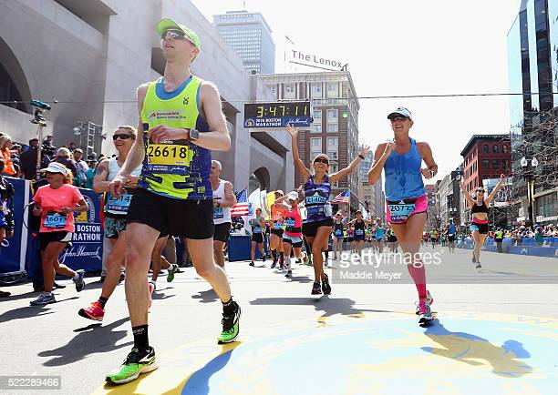 Runners react after crossing the finish line to complete the 120th Boston Marathon on April 18 2016 in Boston Massachusetts