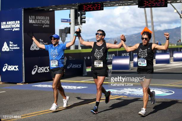Runners react as they cross the finish line of the 2020 Los Angeles Marathon on March 08 2020 in Los Angeles California
