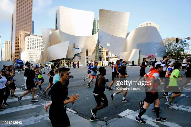 Runners round the corner onto Grand Avenue from 1st Street in front of the Walt Disney Concert Hall during the 2020 Los Angeles Marathon on March 08...