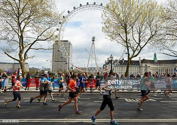 Runners run past the London Eye as they take part in the 2016 London Marathon in central London on April 24 2016 / AFP / NIKLAS HALLE'N