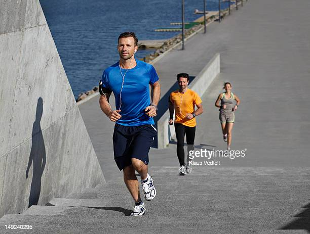 3 runners, running up steps in urban setting