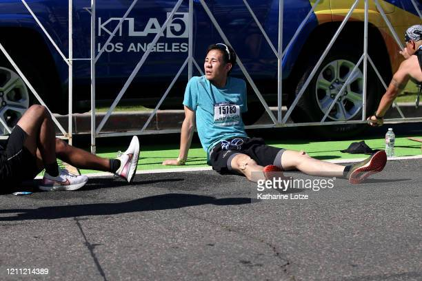 Runners sit after finishing the 2020 Los Angeles Marathon on March 08 2020 in Los Angeles California
