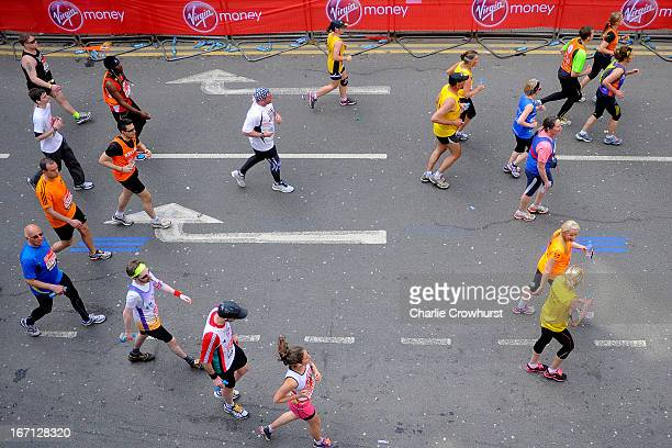 Runners slow up as the make their way through Canary Wharf during the Virgin London Marathon 2013 on April 21 2013 in London England