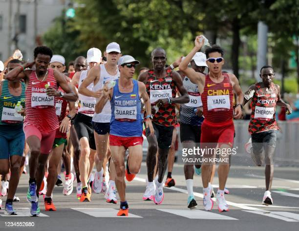 Runners sprinkle water at the refreshment point while competing in the men's marathon final during the Tokyo 2020 Olympic Games in Sapporo on August...