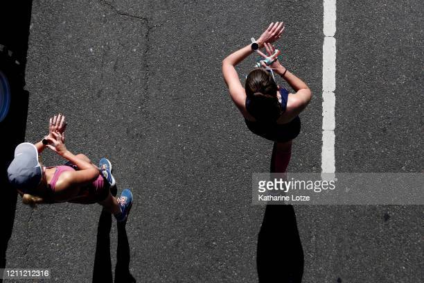 Runners stop their watches after crossing the finish line of the 2020 Los Angeles Marathon on March 08 2020 in Los Angeles California