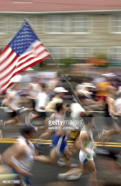 Runners streak by carrying the American flag at the beginning of the 106th running of the Boston Marathon from Hopkinton Massachusetts 15 April 2002...