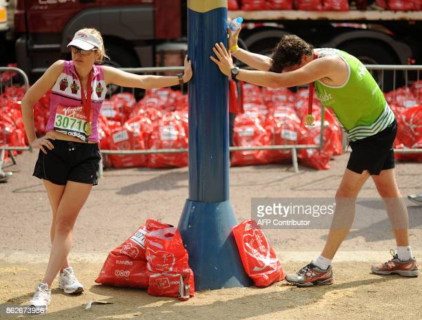 Runners stretch after completing the 2011 London Marathon on April 17, 2011. AFP PHOTO/BEN STANSALL / AFP PHOTO / BEN STANSALL