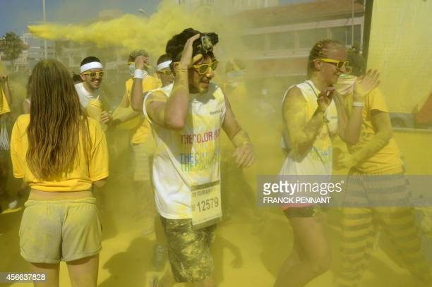 Runners take part in the Color Run on the Prado Beach in Marseille southeastern France on October 4 2014 The Color Run a five kilometers race where...