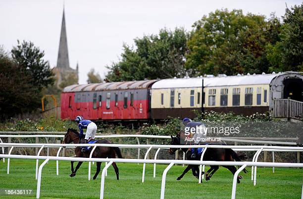 Runners turn out of the back straight in The AJA Fegentri Riders' Handicap Hurdle Race at StratfordUponAvon racecourse on October 31 2013 in...