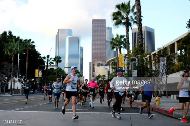 Runners turn the corner onto Temple Street from Grand Avenue during the 2020 Los Angeles Marathon on March 08 2020 in Los Angeles California