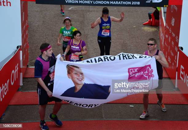 Runners unveil a charity banner at the finish on The Mall during The Virgin London Marathon on April 22 2018 in London England