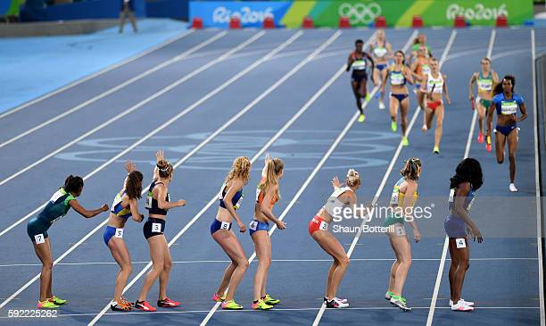 Runners wait for batons to be passed in the first heat of Round One of the Women's 4 x 400m Relay on Day 14 of the Rio 2016 Olympic Games at the...