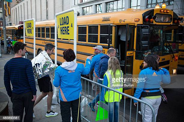 Runners wait in line for a bus to take them to the start of the Boston Marathon in the Boston Commons on April 21 2014 in Boston Massachusetts Today...