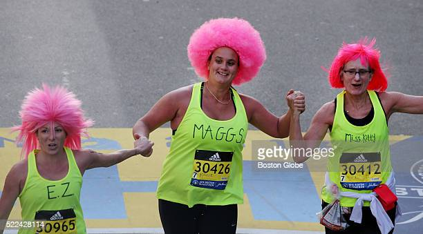 Runners wearing pink wigs cross the finish line of the 120th Boston Marathon on Monday April 18 2016